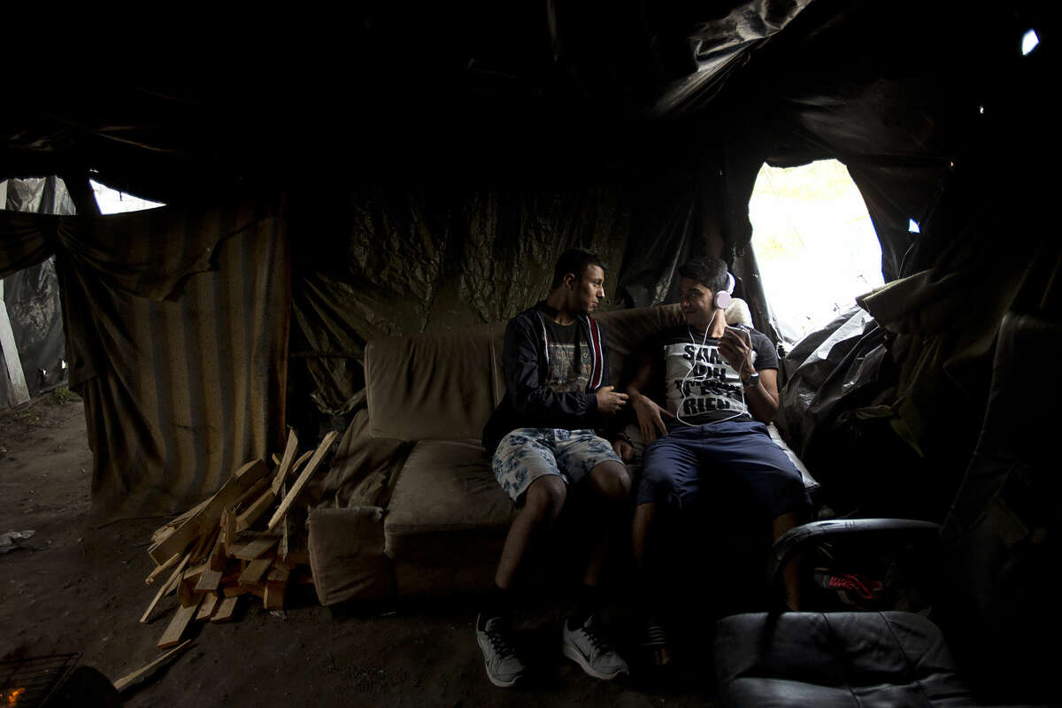 In this Wednesday, Aug. 5, 2015 photo Afghan Zubair Nazari, left, speaks with his friend Abdulrahman as they sit inside their tent at a camp set near Calais, northern France. An estimated 2,500 migrants are currently at the windswept camp surrounded by sand dunes that sprung up when a state-approved day center for migrants was opened nearby. The ramshackle encampment of tents and lean-tos is referred to as the