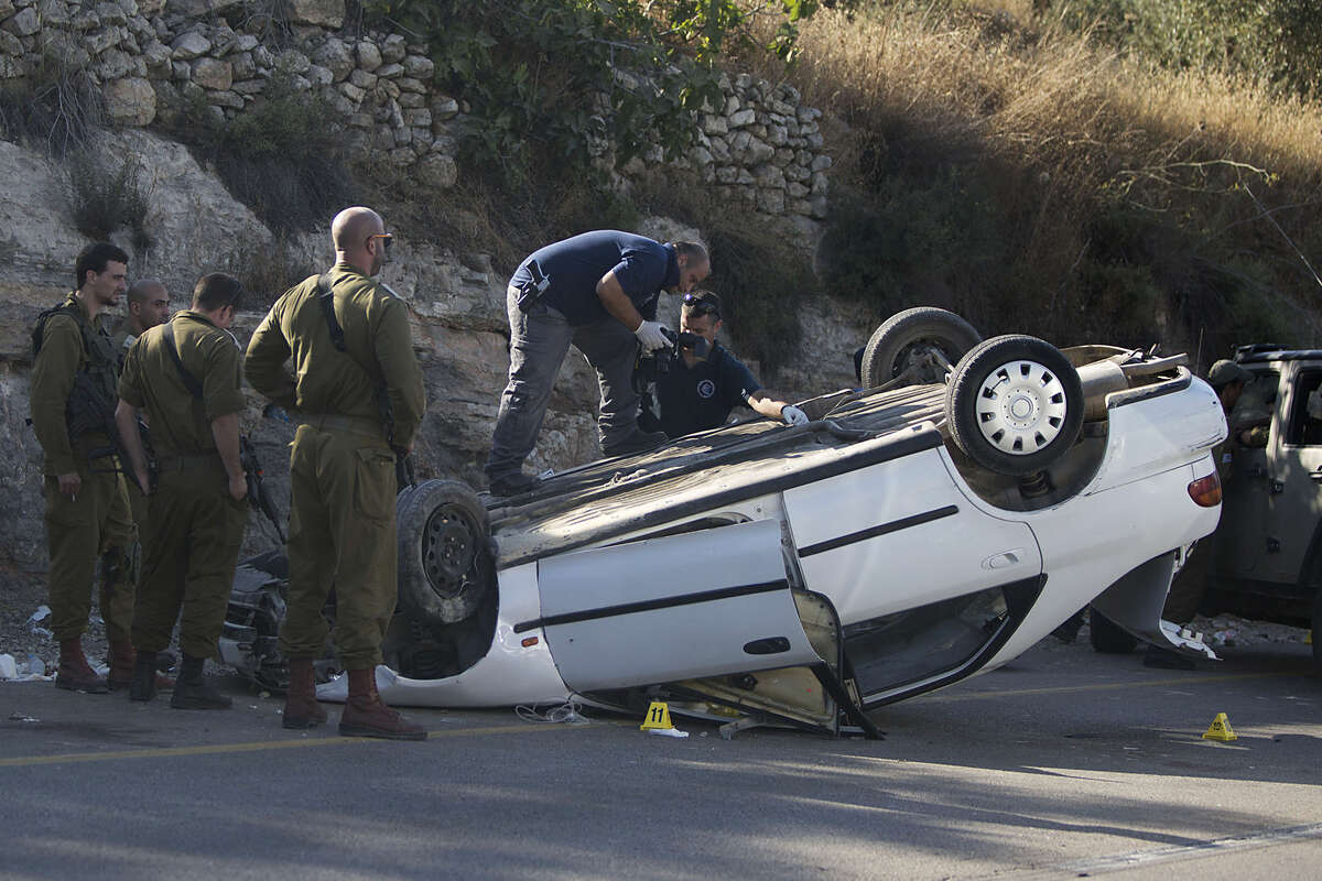 An Israeli forensic policeman inspects the scene of a car attack at a junction midway between Ramallah and Nablus near the West Bank Jewish settlement of Shilo, Thursday, Aug 6, 2015. A Palestinian motorist rammed his car into pedestrians near the West Bank Jewish settlement of Shilo, wounding three Israelis before he was shot by Israeli troops, the military said. (AP Photo/Majdi Mohammed)