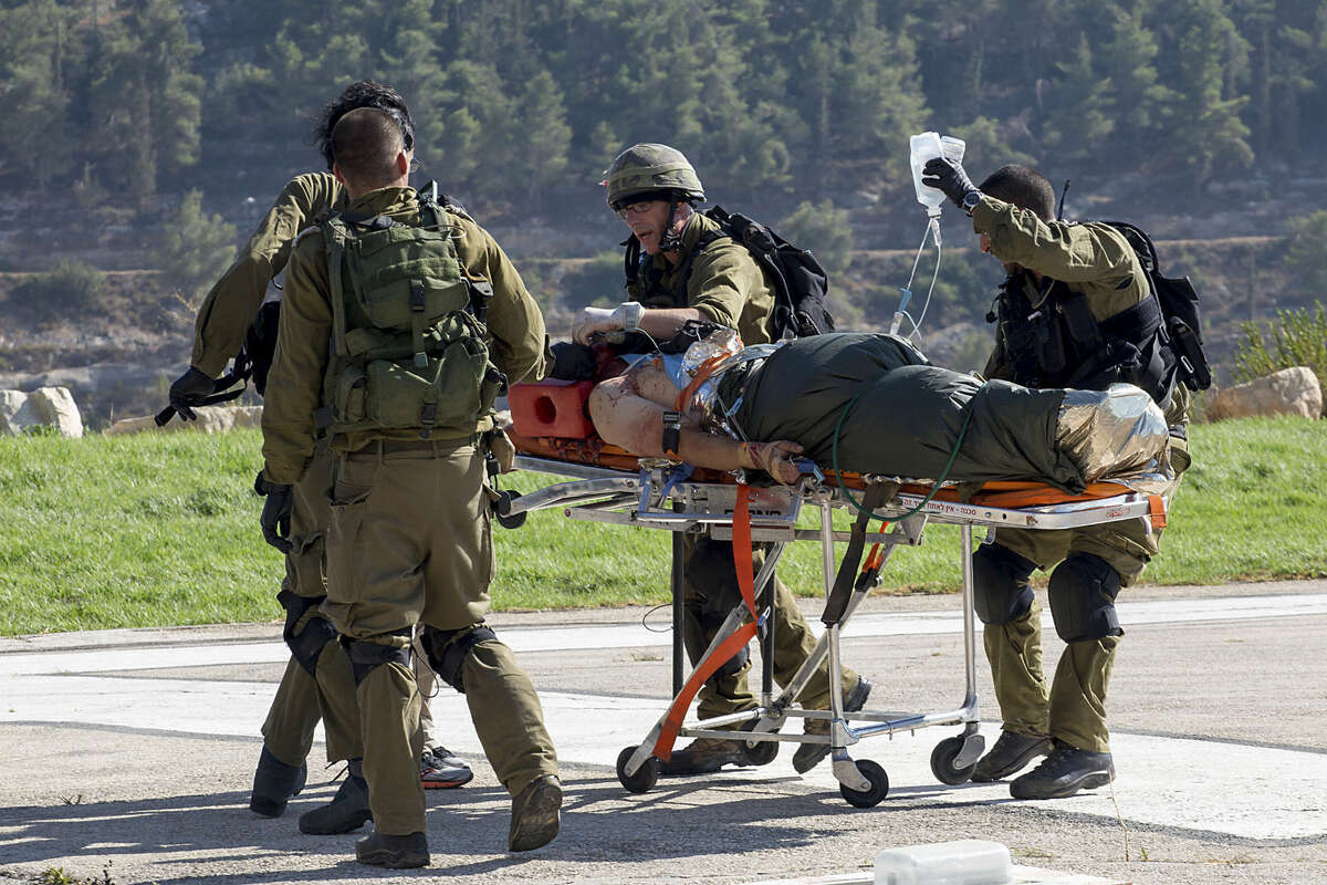 Israeli soldiers transport a wounded Israeli man to Hadassah Ein Kerem Hospital in Jerusalem after he was evacuated by helicopter, Thursday, Aug 6, 2015. A Palestinian motorist rammed his car into pedestrians near the West Bank Jewish settlement of Shilo, wounding three Israelis before he was shot by Israeli troops, the military said. (AP Photo/Emeil Salman) ****ISRAEL OUT***