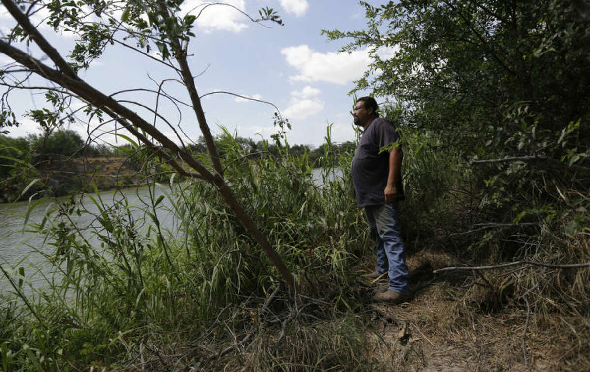 In this June 20, 2014 photo, Napoleon Garza stands on his property along the Rio Grande at a site where immigrants cross the U.S.-Mexico border illegally in Granjeno, Texas. Just since October, the Border Patrol?'s Rio Grande Valley sector has made more than 194,000 arrests, nearly triple that of any other sector. Most are from Central America, and many are children. (AP Photo/Eric Gay)