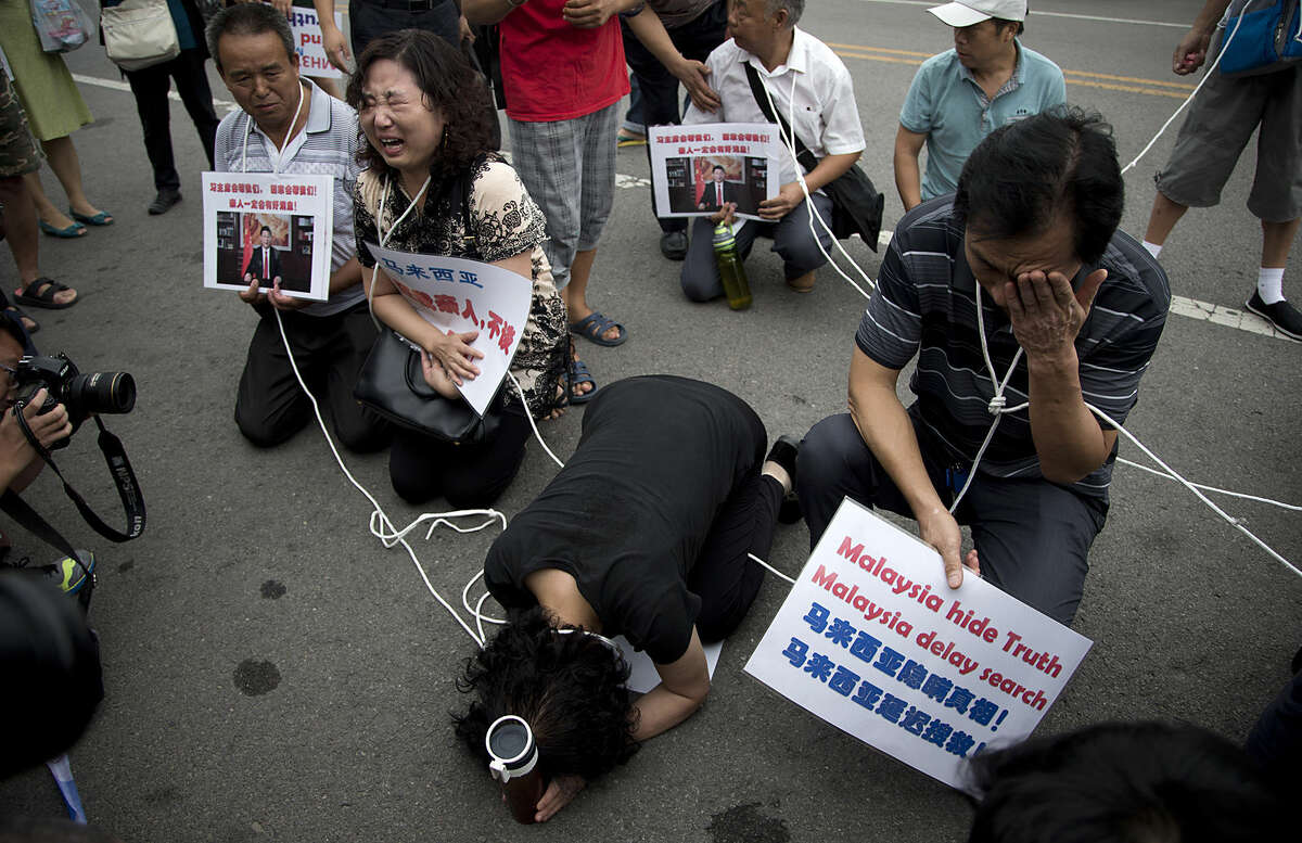 Relatives of the passengers aboard Malaysia Airlines Flight 370 that went missing on March 8, 2014, kneel down as they cry in front of the media ahead of a briefing given by the airlines outside a help center in Beijing Friday, Aug. 7, 2015. Families aching for closure after their relatives disappeared aboard the flight vented deep frustration Thursday at differing statements from Malaysia and France over whether the finding of a plane part had been confirmed. (AP Photo/Andy Wong)