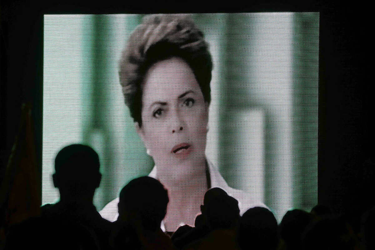 Militants of the Workers Party watch a speech by Brazil's President Dilma Rousseff, which was broadcast on the Workers Party's television program, in Brasilia, Brazil, Thursday, Aug. 6, 2015. A new poll shows Rousseff's approval rating at a new low and the number of people favoring her impeachment growing. (AP Photo/Eraldo Peres)