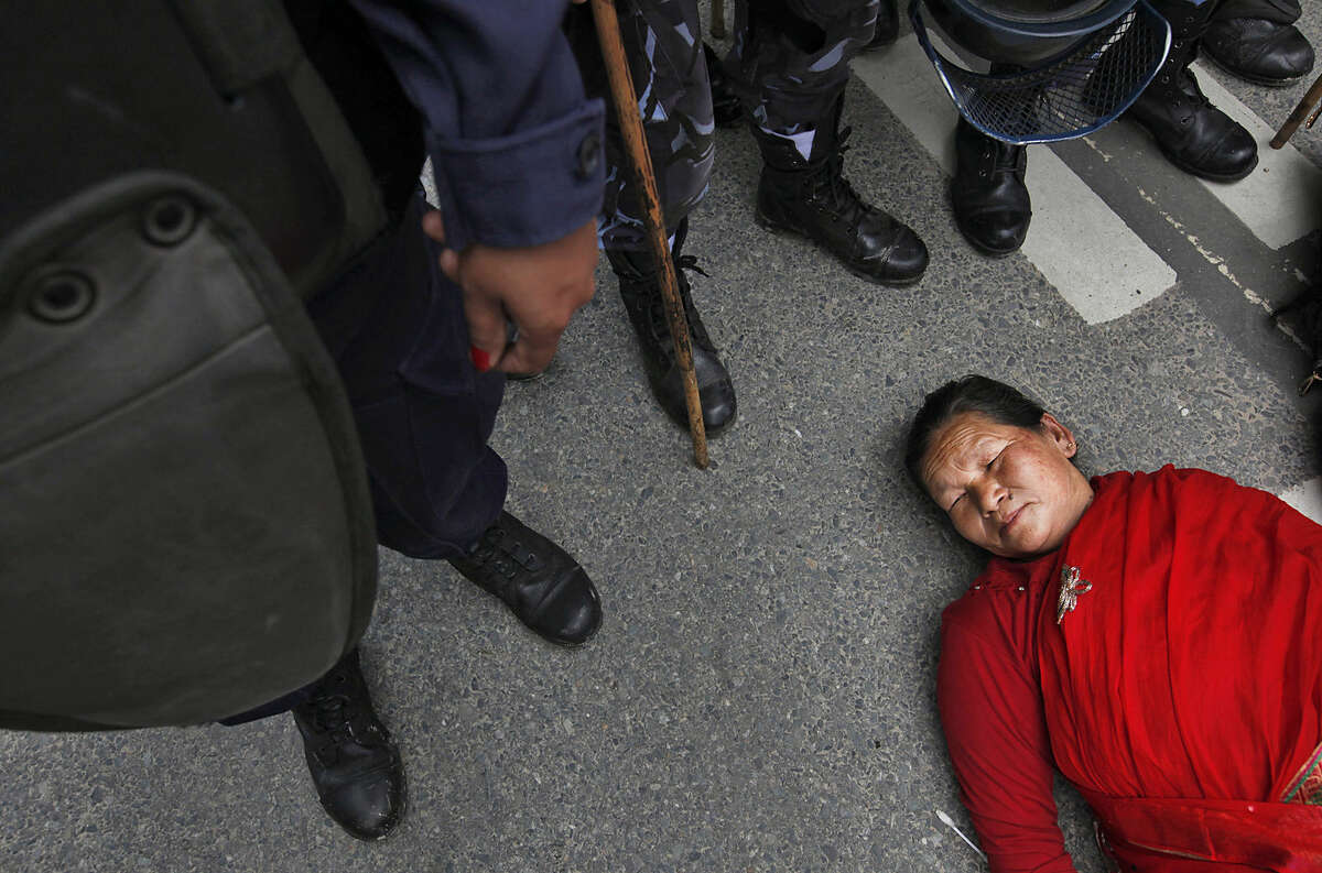 A Nepalese woman lies on the ground as she acts to sleep during a protest demanding provision in the new constitution to avail citizenship in the name of one's mother, in Kathmandu, Nepal, Friday, Aug. 7, 2015. Nepal's proposed new constitution has sparked fury from women who protested against the denial of citizenship rights to children if their fathers are not Nepalese citizens. While Nepal's new constitution promises full citizenship to all children with one Nepalese parent, the laws are routinely flouted when only the mother is a citizen. (AP Photo/Niranjan Shrestha)