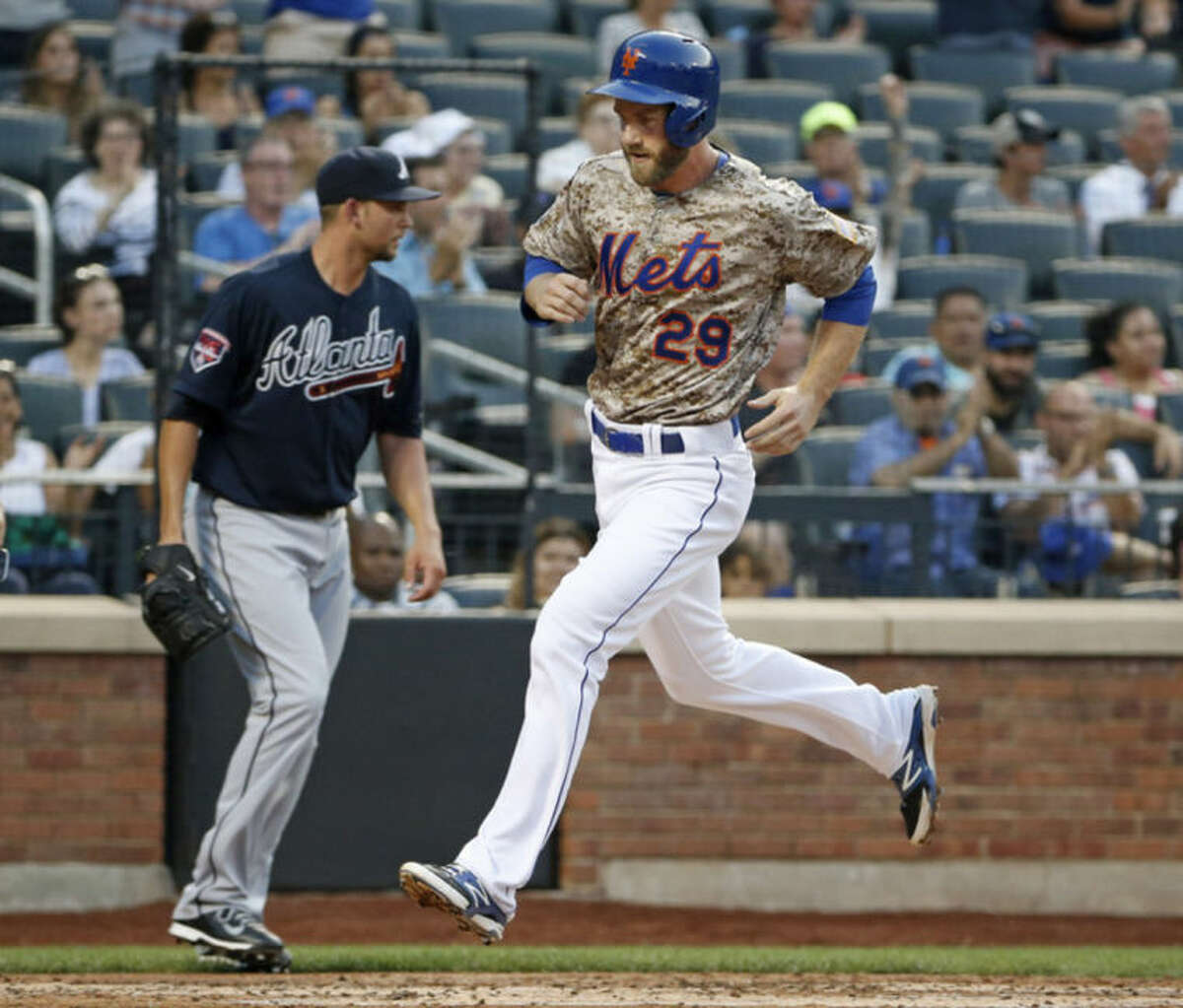 New York Mets Eric Campbell, right, scores on Travisd d'Arnaud's second-inning RBI double off Atlanta Braves starting pitcher Mike Minor, left, in a baseball game in New York, Monday, July 7, 2014. (AP Photo/Kathy Willens)