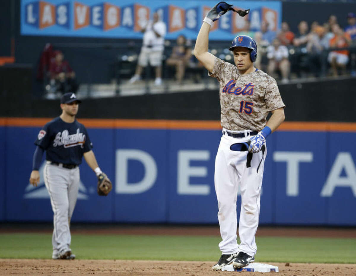 New York Mets Travis d'Arnaud waves his batting gear over his head after hitting a run-scoring, second-inning, double off Atlanta Braves starting pitcher Mike Minor in a baseball game in New York, Monday, July 7, 2014. (AP Photo/Kathy Willens)