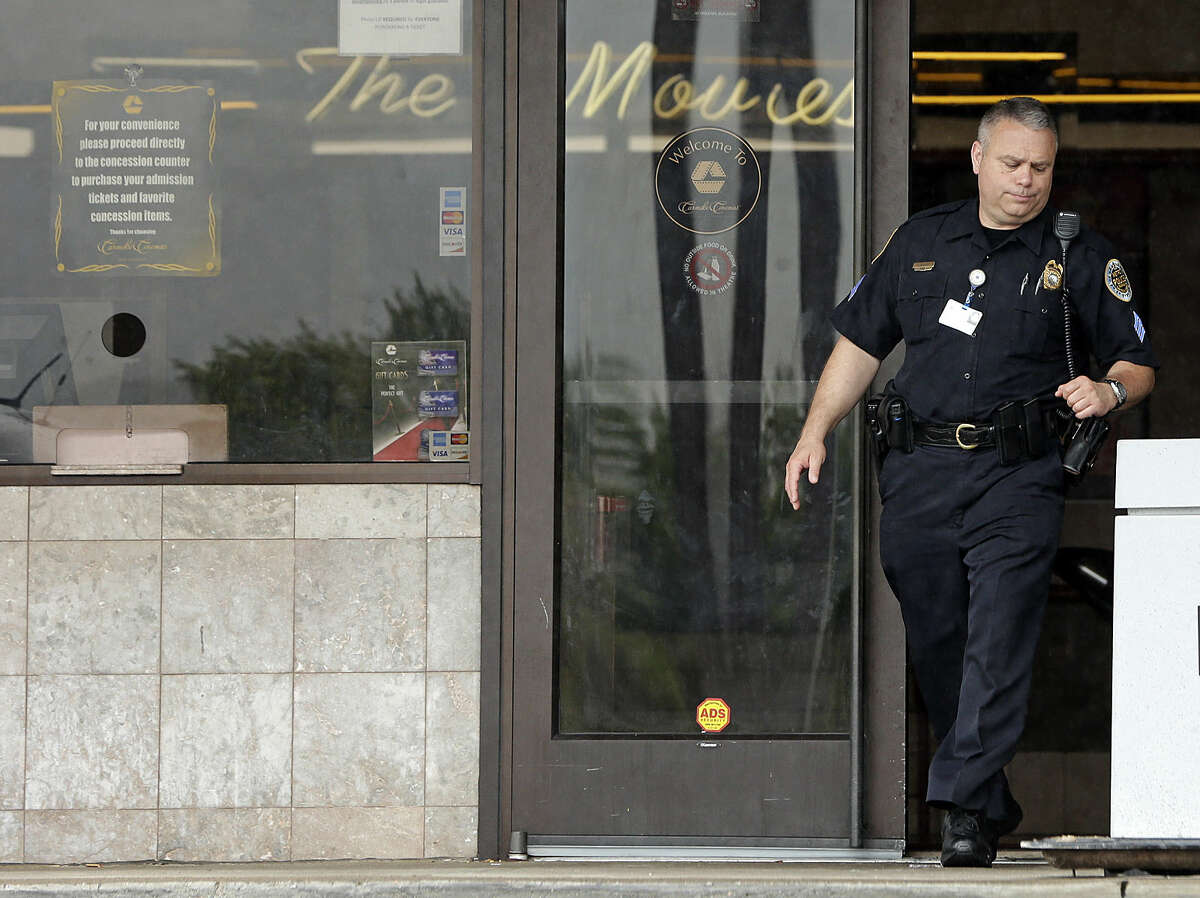A police officer leaves the lobby of a movie theater complex Thursday, Aug. 6, 2015, in Antioch, Tenn., where an investigation continues after police respond to an attacker Wednesday. What initially appeared to be another mass shooting at a movie theater ended up being an attack by a disturbed homeless man who wasn't armed with a real gun and was eventually shot and killed by police. (AP Photo/Mark Humphrey)