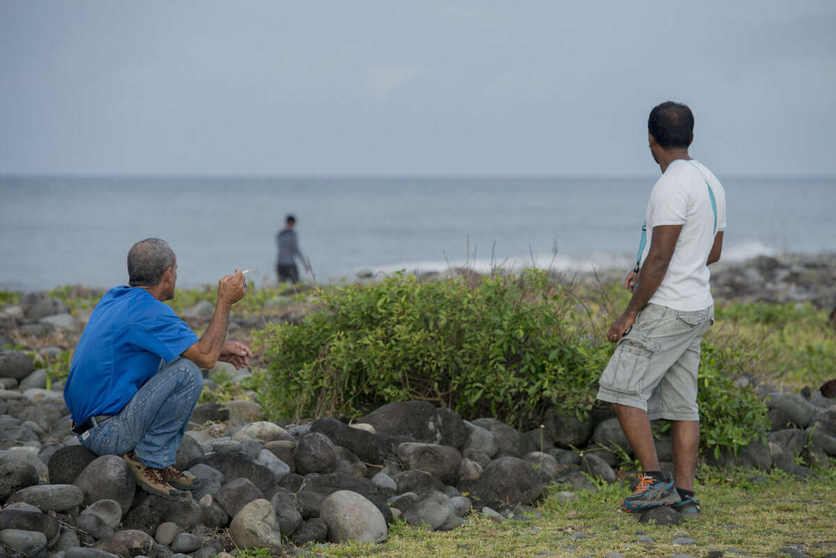 People walk on the beach of Saint-Andre, Reunion Island, in the hope of finding more plane debris, Thursday, Aug 6, 2015. Malaysian Prime Minister Najib Razak announced on Aug. 6 the washed-up debris was part of the wreckage of the missing Malaysian Airlines flight MH370. (AP Photo/Fabrice Wislez)