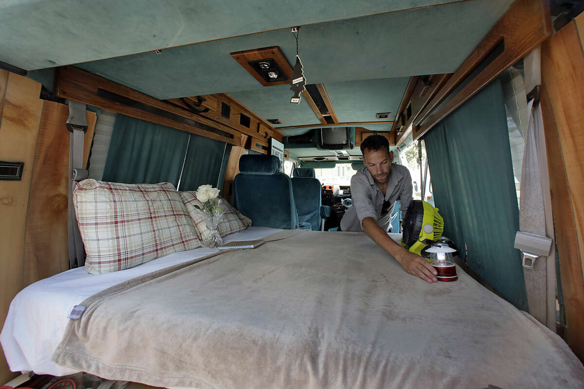 In this Monday, Aug. 3, 2015, photo, Jonathan Powley, who rents parked vehicles on Airbnb, prepares a 1995 Chevrolet conversion van, one of his offerings, in the Queens borough of New York. While parked vehicles make up only a fraction of the thousands of Airbnb listings in New York City, they provide an option for adventurous, budget-minded visitors seeking a place for far less than the $200-and-up most hotels charge. (AP Photo/Richard Drew)
