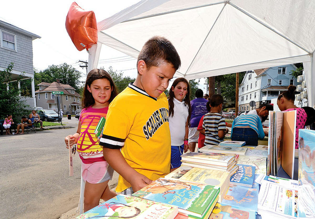 Hour photo / Erik Trautmann Noelia Ramos and Jordan Chenchella look over books dontaed by the South Norwalk Branch Library during the Bouton Street block party Saturday where school supplies donated by Staples and The Hour were given to neighborhood children.