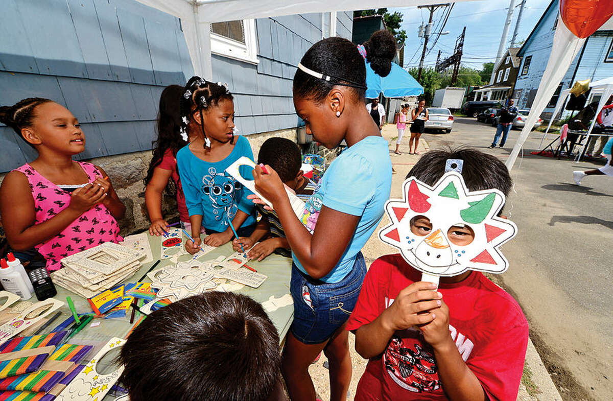 Hour photo / Erik Trautmann John Garcia, 6, colors a craft mask during the Bouton Street block party Saturday where school supplies donated by Staples and The Hour were given to neighborhood children.
