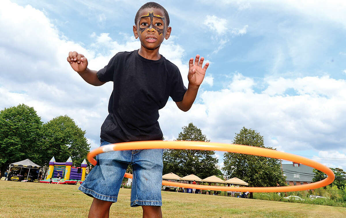 Hour photo / Erik Trautmann Marquel Polk tries the hula hoop during the annual Sono Day Out at Ryan Park in South Norwalk Saturday.