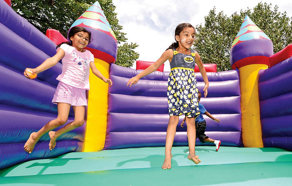 Hour photo / Erik Trautmann Aminha amd Sana Bahora jump in the inflatable castle during the annual Sono Day Out at Ryan Park in South Norwalk Saturday.