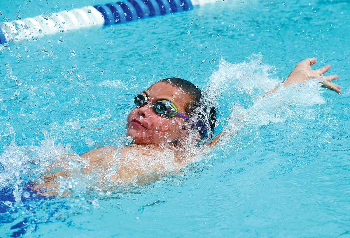 Hour photo / Erik Trautmann Jusin Lewis swims the 10 and Under 25M Backstroke for the Lake Club during the Fairfield County Swim League Championship meet at Roxbury Country Club in Stamford Saturday.