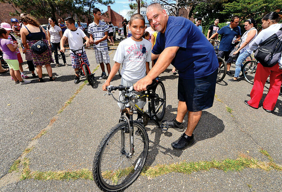 Hour photo / Erik Trautmann Norwalk Police officer Hector Delgado and 2wheels.org give away over 50 bicycles including one to James Gross, 10, during the annual Sono Day Out at Ryan Park in South Norwalk Saturday.