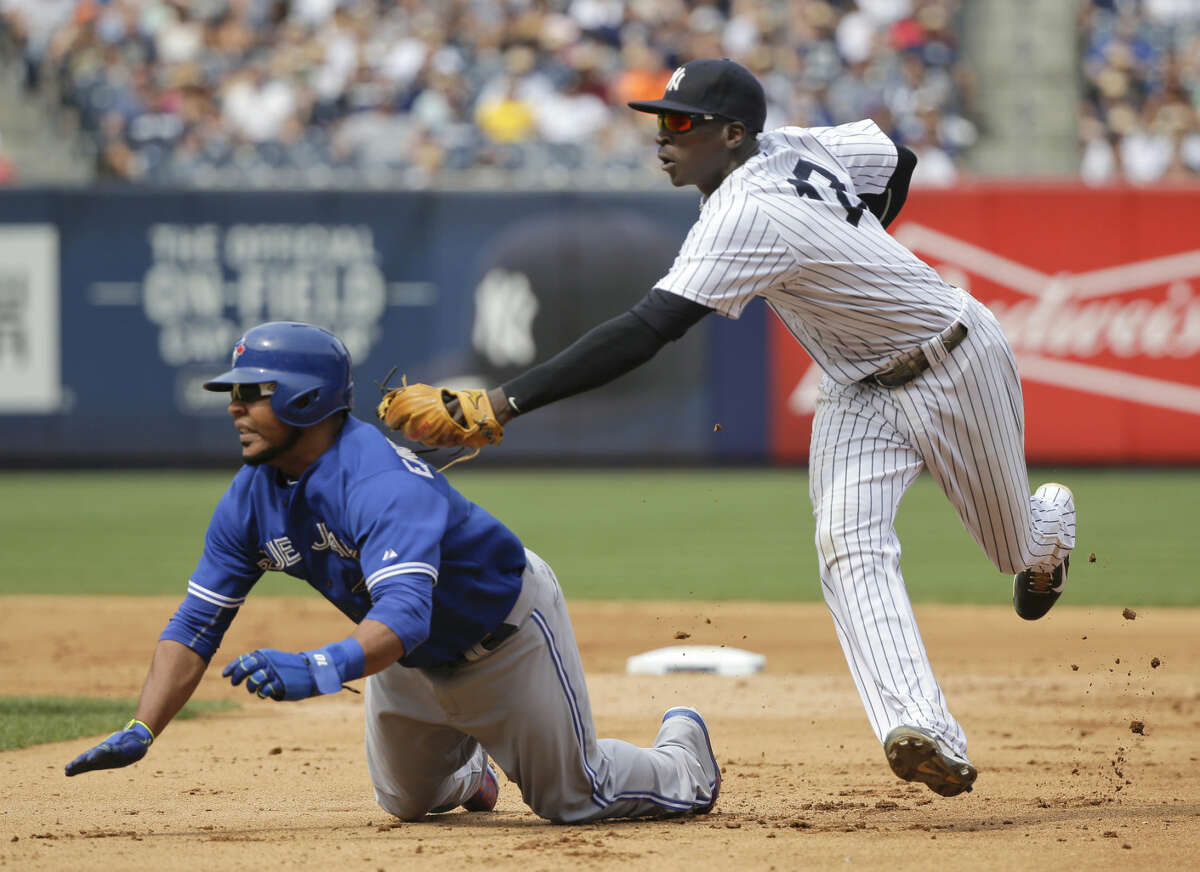 New York Yankees shortstop Didi Gregorius makes a double play as he tags out Toronto Blue Jays' Edwin Encarnacion between first and second base before flipping the ball to first for the force out on Toronto Blue Jays Justin Smoak during the eighth inning of a baseball game, Saturday, Aug. 8, 2015, in New York. (AP Photo/Julie Jacobson)