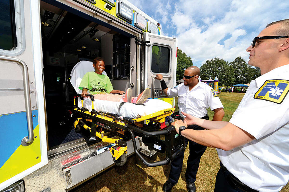 Hour photo / Erik Trautmann Simone King, 8, gets a ride in a gurney from Norwalk Hospitals EMTs Danny Monahan and David Jean-Jacques during the annual Sono Day Out at Ryan Park in South Norwalk Saturday.