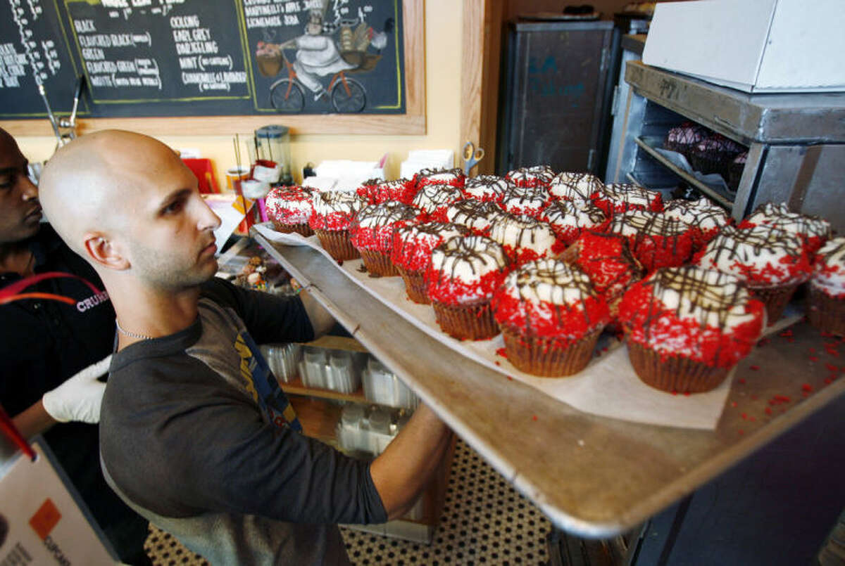 FILE - In this Sept. 20, 2007 file photo, Crumbs Bake Shop managing partner Harley Bauer carries of tray of cupcakes during the store's grand opening in Beverly Hills, Calif. Crumbs on Monday, July 7, 2014 said it is shuttering all its stores, a week after the struggling cupcake shop operator was delisted from the Nasdaq. (AP Photo/Matt Sayles, File)