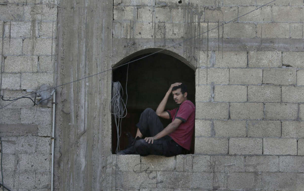 A Palestinian looks at a destroyed house after an Israeli missile strike in Khan Younis, Gaza Strip, Tuesday, July 8, 2014. The Israeli military launched what could be a long-term offensive against the Hamas-ruled Gaza Strip on Tuesday, striking sites in Gaza and mobilizing troops for a possible ground invasion aimed at stopping a heavy barrage of rocket attacks against Israel. (AP Photo/Khalil Hamra)