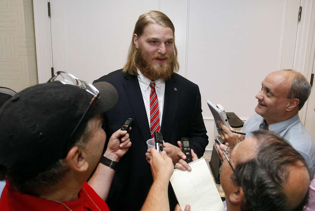 Connecticut tackle Andreas Knappe, center, speaks with reporters at the American Athletic Conference NCAA college football media days in Newport, R.I., Tuesday, Aug. 4, 2015. (AP Photo/Stew Milne)