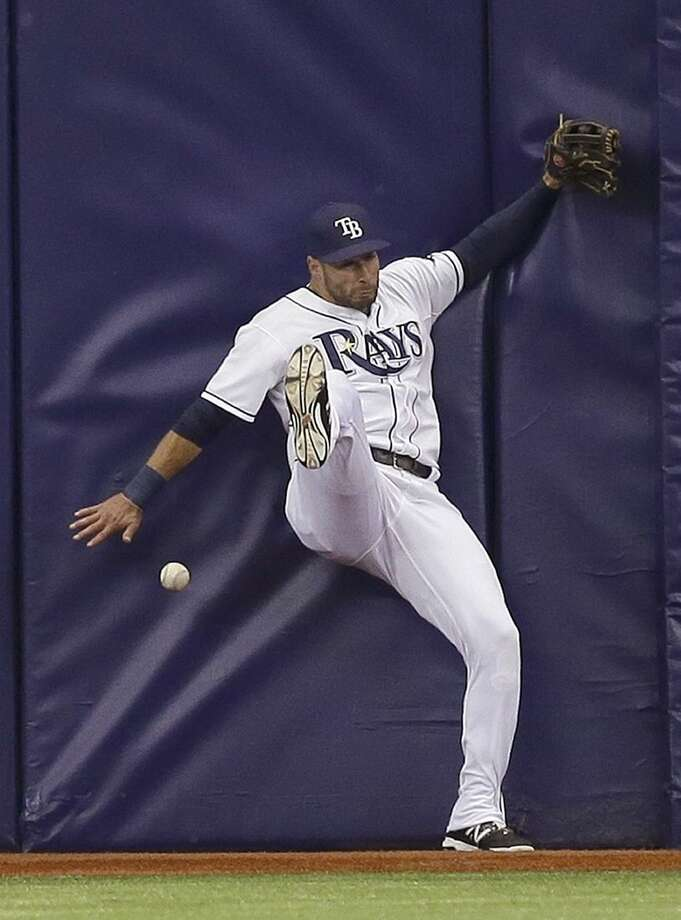 Tampa Bay Rays center fielder Kevin Kiermaier hits the wall but cannot catch a two-run double by New York Mets' Lucas Duda off Rays pitcher Nathan Karns during the first inning of an interleague baseball game Saturday, Aug. 8, 2015, in St. Petersburg, Fla. Mets' Daniel Murphy and Yoenis Cespedes scored on the hit. (AP Photo/Chris O'Meara)