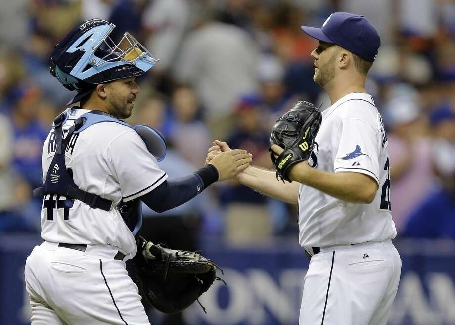 Tampa Bay Rays relief pitcher Brad Boxberger, right, shakes hands with catcher Rene Rivera after closing out the New York Mets during the ninth inning of an interleague baseball game Saturday, Aug. 8, 2015, in St. Petersburg, Fla. The Rays won the game 5-4. (AP Photo/Chris O'Meara)