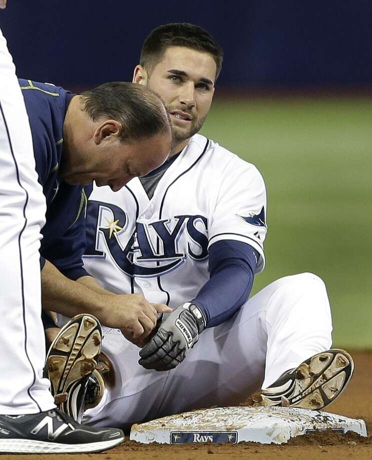 Tampa Bay Rays trainer Ron Porterfield, left, looks at Kevin Kiermaier's finger after he got hurt sliding into second base after a two-run single off New York Mets starting pitcher Noah Syndergaard during the first inning of an interleague baseball game Saturday, Aug. 8, 2015, in St. Petersburg, Fla. Kiermaier remained in the game. (AP Photo/Chris O'Meara)