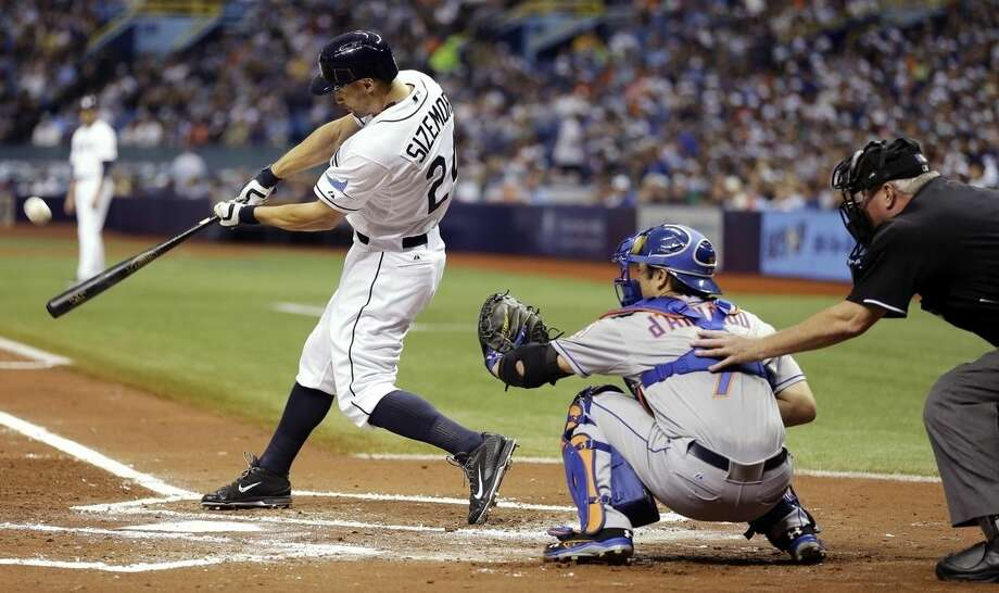 Tampa Bay Rays' Grady Sizemore (24) connects for a home run off New York Mets starting pitcher Noah Syndergaard during the first inning of an interleague baseball game Saturday, Aug. 8, 2015, in St. Petersburg, Fla. Mets catcher Travis d'Arnaud, center, looks on. (AP Photo/Chris O'Meara)
