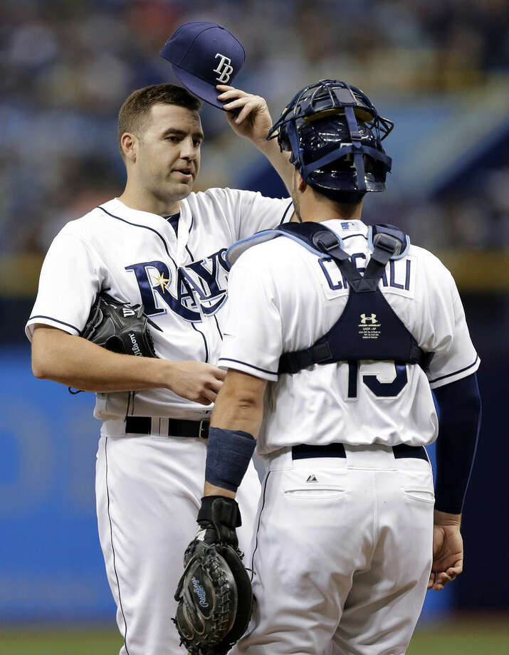 Tampa Bay Rays starting pitcher Nathan Karns, left, takes off his hat as he talks to catcher Curt Casali during the first inning of a baseball game against the New York Mets on Saturday, Aug. 8, 2015, in St. Petersburg, Fla. (AP Photo/Chris O'Meara)