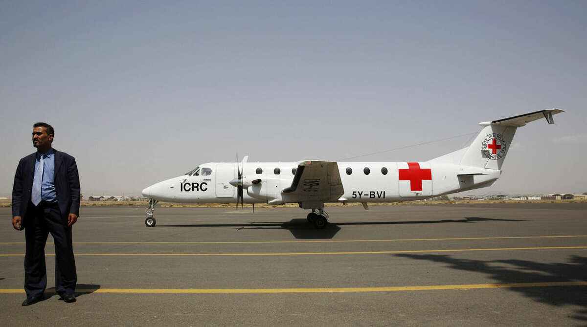 A Yemeni airport security official stands by a plane of the International Committee of the Red Cross on the tarmac of the international airport in Sanaa, Yemen, Saturday, Aug. 8, 2015. (AP Photo/Hani Mohammed)