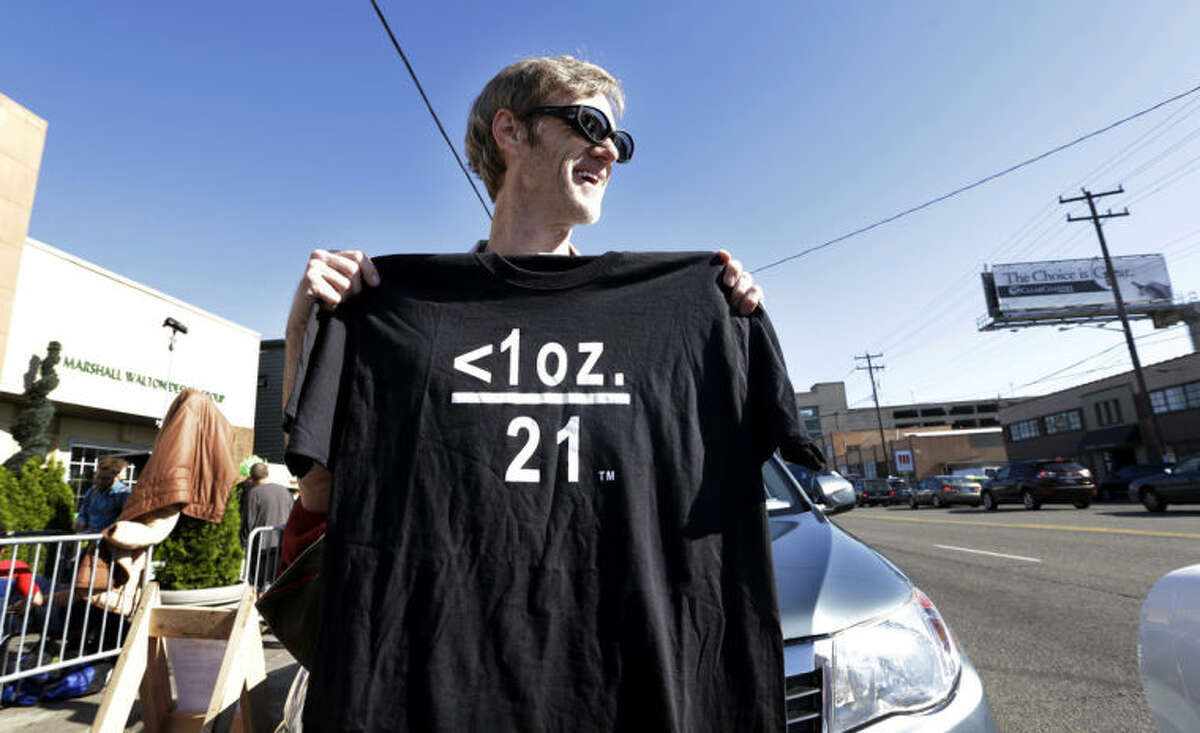 Terry Martin displays a tee shirt he's selling celebrating legal marijuana in front of Cannabis City, as he waits with others on the first day that sales of recreational pot is legal in the state Tuesday, July 8, 2014, in Seattle. The symbols translate that under one ounce of pot and over 21-years of age means that it's legal. The shop is the first and, initially, only store in Seattle to legally sell pot. (AP Photo/Elaine Thompson)