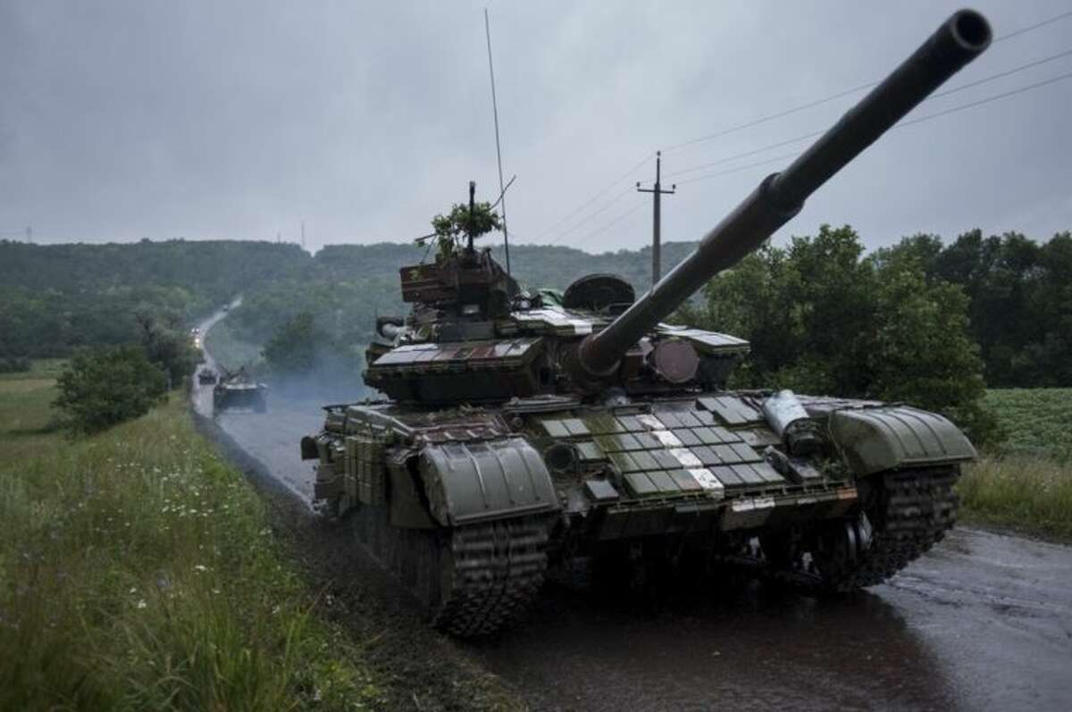 Ukrainian tanks roll to the base in Devhenke village, Kharkiv region, eastern Ukraine, Monday, July 7, 2014. There was no word Monday from Ukrainian President Petro Poroshenko, who had promised to start negotiations on a new cease-fire last week. A contact group for the Organization for Security and Co-operation in Europe met in Kiev on Sunday to discuss the situation in Donetsk, but no representatives from the rebels attended and no breakthroughs were announced. (AP Photo/Evgeniy Maloletka)