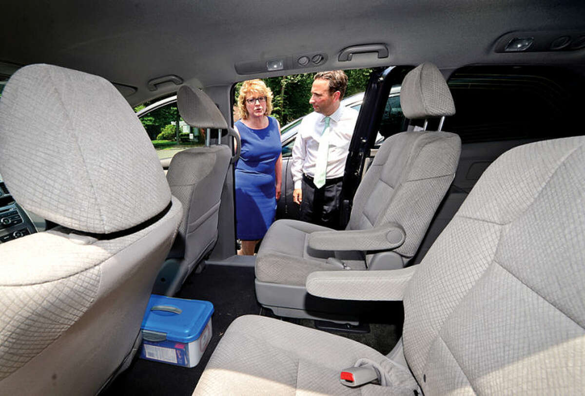 Hour photo / Erik Trautmann State Senator Bob Duff and STAR Inc. Executive Director Katie Banzhaf, examine one of the minivans purchased through Governor Malloy's Nonprofit Grant Program during a brief press conference Tuesday.