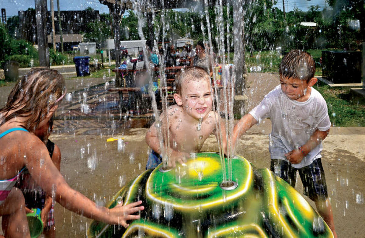 Hour photo / Erik Trautmann 4 year old Jace Cassara, center, cools off at the spash pad at Devon's Place playground Tuesday. The rest of the week will continue to be hot and humid with temperatures in the 80s.
