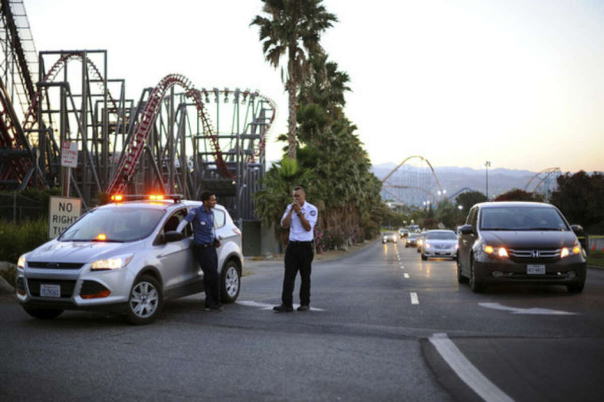 In this photo taken on Monday, July 7, 2014, members of the Six Flags Magic Mountain amusement park security staff monitor the situation at the exit of the park after riders were injured on the Ninja coaster, not shown, in Valencia, Calif. The roller coaster hit a tree branch dislodging the front car, leaving four people slightly injured and keeping nearly two dozen summer fun-seekers hanging 20 to 30 feet in the air for hours as day turned to night. (AP Photo/Los Angeles Daily News, Andy Holzman)