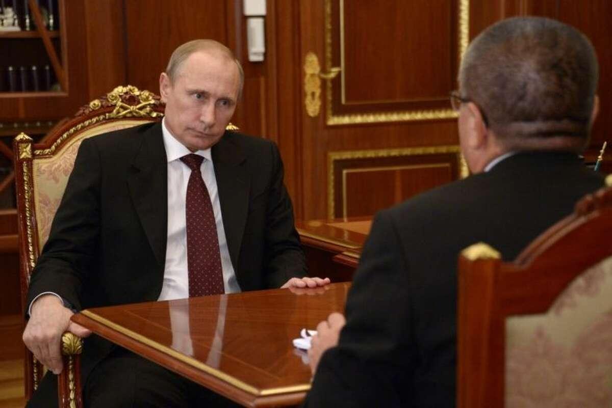 Russian President Vladimir Putin listens Russia's economic development minister Alexei Ulyukayev, right, in Moscow's Kremlin on Monday, July 7, 2014. (AP Photo/RIA Novosti, Alexei Nikolsky, Presidential Press Service)
