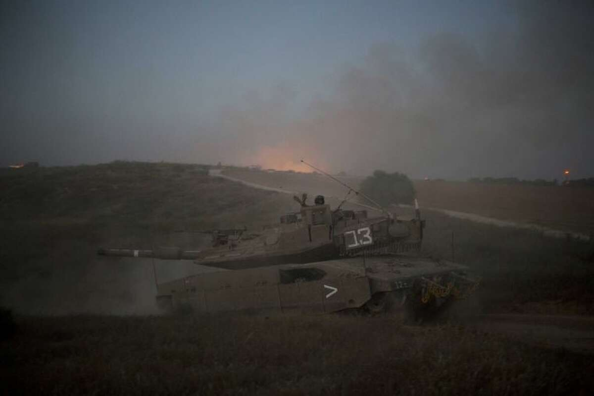 Israeli soldiers wave from a tank moving into position on the Israel-Gaza Border, Tuesday, July 8, 2014. The Israeli military launched a major offensive in the Hamas-ruled Gaza Strip on Tuesday, striking more than 100 sites and mobilizing troops for a possible ground invasion in what Israel says is an operation aimed at stopping a heavy barrage of rocket attacks from the Palestinian territory. (AP Photo/Ariel Schalit)