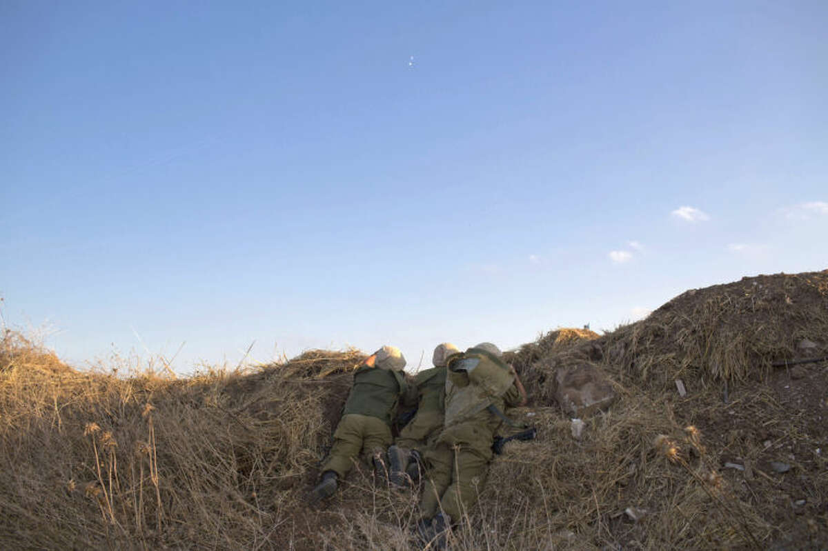 Israeli soldiers take cover as missile defense systems detect incoming rocket fire in Tel Aviv, Israel, Thursday, July 8, 2014. The Israeli military launched what could be a long-term offensive against the Hamas-ruled Gaza Strip on Tuesday striking sites in Gaza and mobilizing troops for a possible ground invasion aimed at stopping a heavy barrage of rocket attacks against Israel. (AP Photo/Oded Balilty)