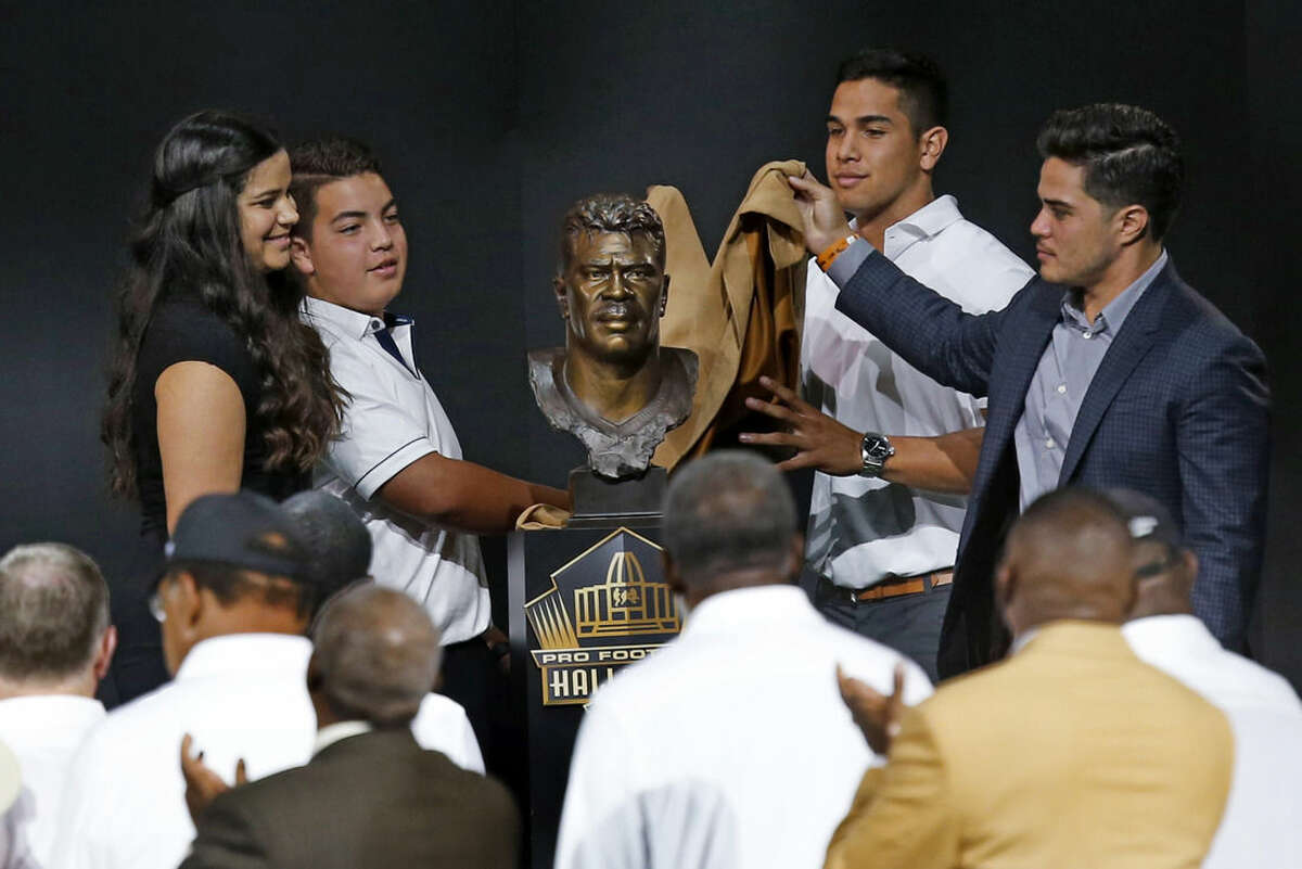 Children of former NFL player Junior Seau, from left, Sydney, Hunter, Jake, and Tyler, unveil the bust of their late father during an induction ceremony at the Pro Football Hall of Fame on Saturday, Aug. 8, 2015, in Canton, Ohio. (AP Photo/Tom E. Puskar)