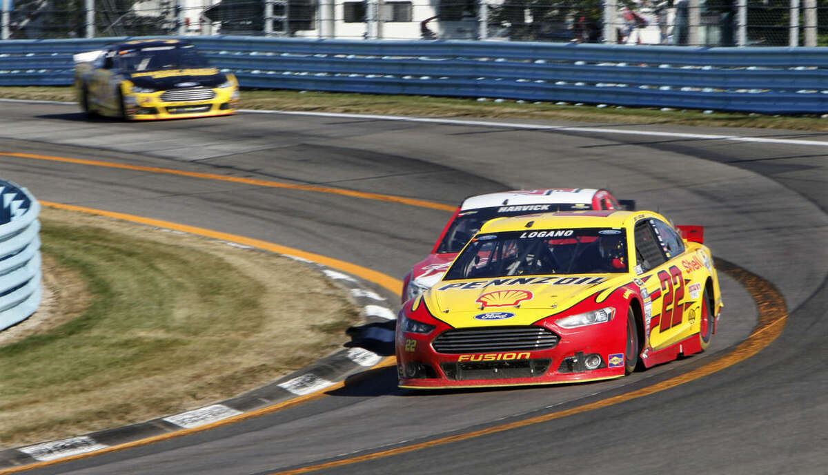 Joey Logano (22) passes Kevin Harvick coming into the last turn on the way to winning a NASCAR Sprint Cup series auto race at Watkins Glen International, Sunday, Aug. 9, 2015, in Watkins Glen, N.Y. (AP Photo/Douglas Ford Rea)