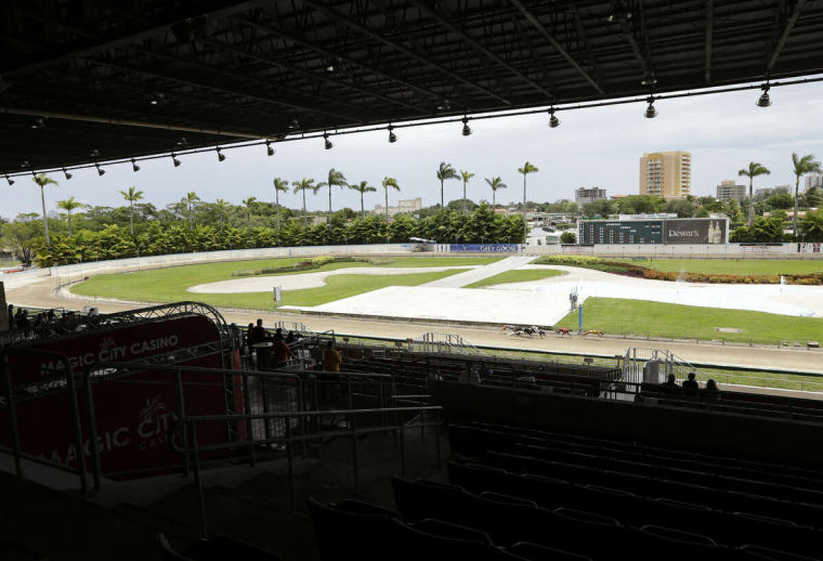 In this Tuesday, June 17, 2014, photo, empty seats are visible while greyhounds race at the Flagler Dog Track in Miami. Greyhound racing used to be a popular sport in the United States, but in recent years it has fallen out of favor with gamblers and aficionados. (AP Photo/Lynne Sladky)