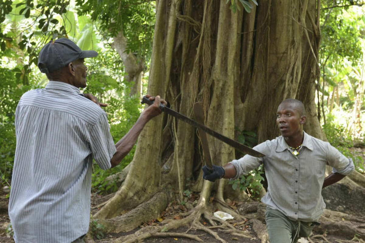 In this July 2, 2014, photo, Haitian machete fencing expert Alfred Avril, left, instructs his son Roland in the little-known martial art of machete fencing, outside Jacmel, Haiti. Trying to bring the secretive, rural Haitian martial art to foreigners involves certain trade-offs, but Avril is now eager to share his machete-fighting expertise with anyone who is interested. The former Haitian army drill instructor trained his sons, grandsons and neighbors to carry on his school. (AP Photo/David McFadden)