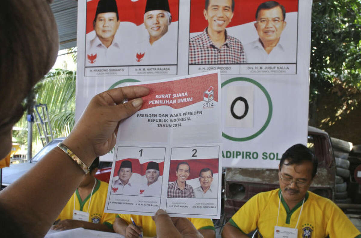 A woman checks her ballot before casting her vote in the presidential election at a polling station in Solo, Central Java, Indonesia, Wednesday, July 9, 2014. (AP Photo/Taufan Wijaya)