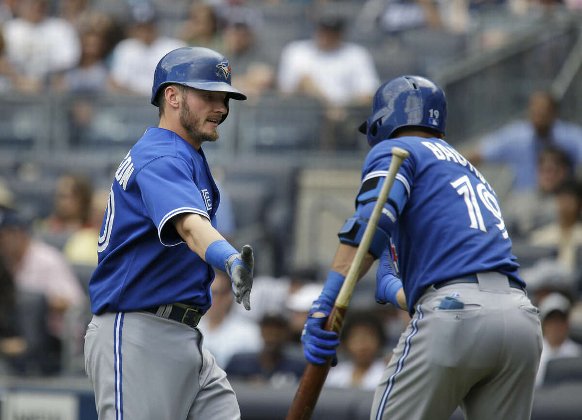 Toronto Blue Jays' Jose Bautista, right, greets Josh Donaldson after Donaldson hit a home run during the first inning of the baseball game against the New York Yankees at Yankee Stadium, Sunday, Aug. 9, 2015, in New York. (AP Photo/Seth Wenig)