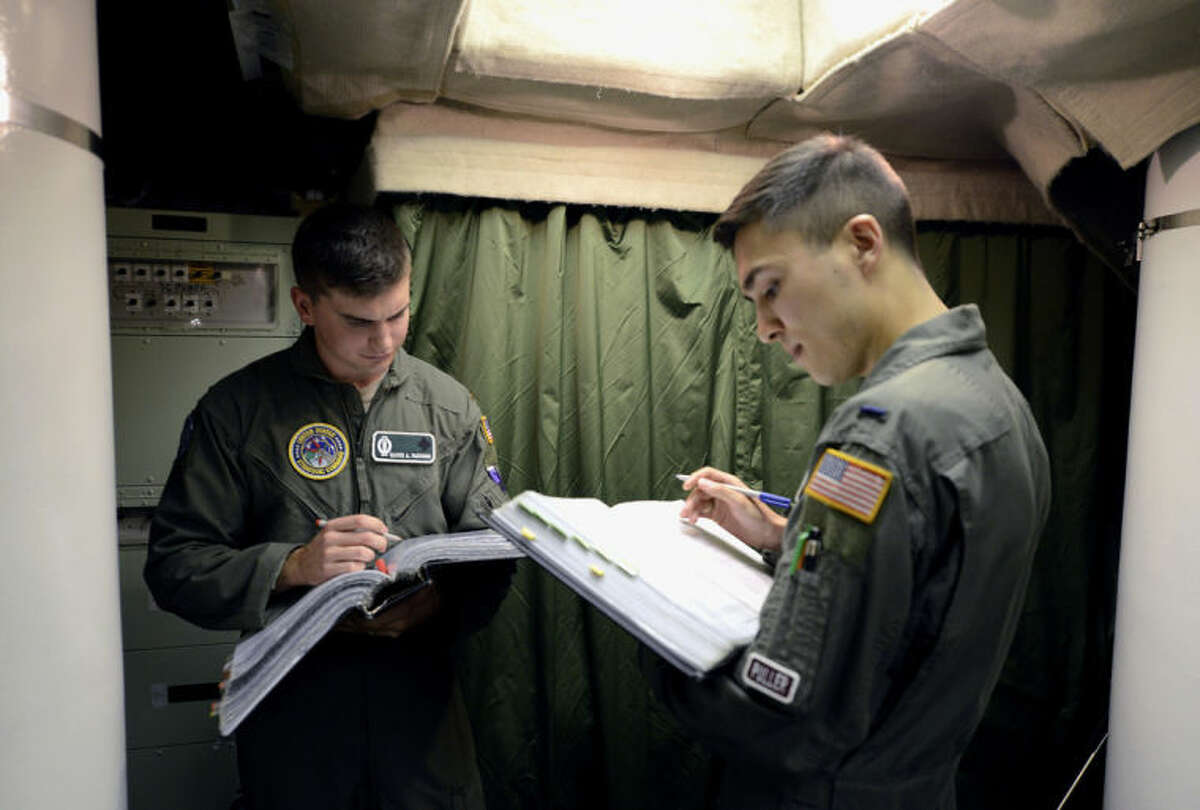 In this photo taken June 24, 2014, 2nd Lt. Oliver Parsons, left, and 1st Lt. Andy Parthum go through a checklist in the underground control room where they work a 24-hour shift at an ICBM launch control facility near Minot, N.D., on the Minot Air Force Base. The crew is responsible for controlling and launching the 10 nuclear-tipped Minuteman 3 missiles located in remote launch sites under their command. (AP Photo/Charlie Riedel)