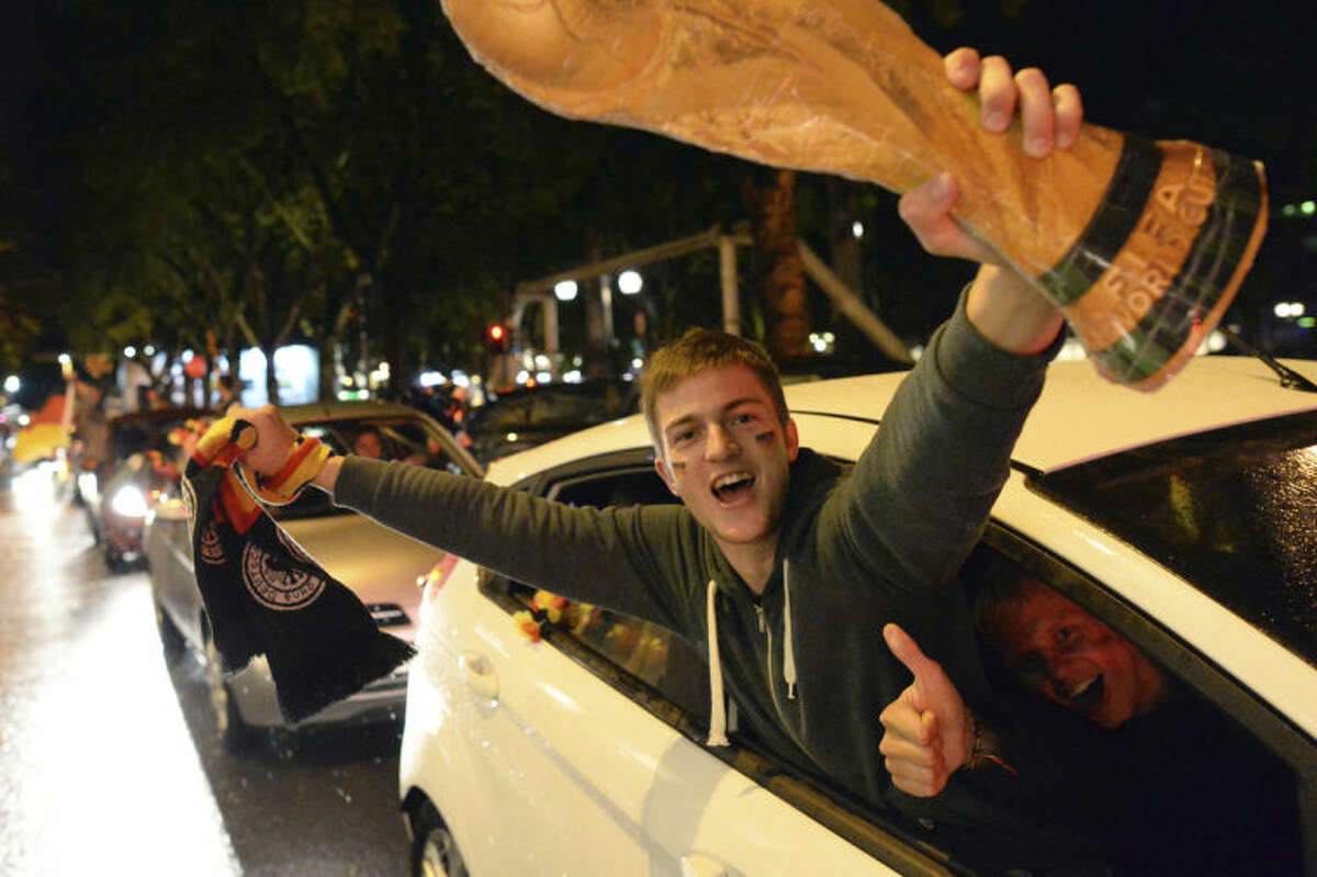 Soccer fans celebrate with a mock World Cup trophy in Duesseldorf, western Germany, Tuesday evening, July 8, 2014, after Germany beat Brazil 7-1 in their semifinal soccer match of the 2014 World Cup in Brazil. (AP Photo/dpa, Matthias Balk)