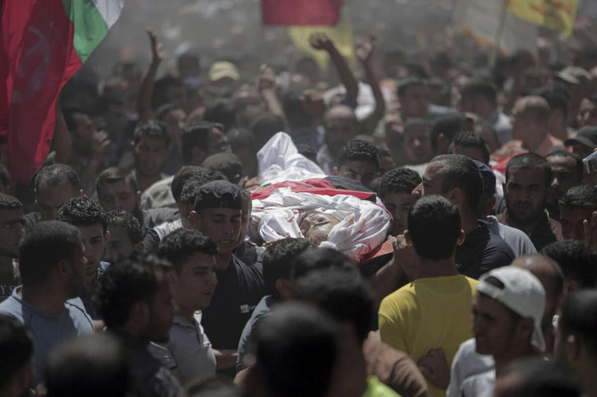 Palestinian mourners carry bodies of the five members of Hamad family who were killed in an Israeli missile strike late Tuesday, in town of Beit Hanoun, northern Gaza Strip, Wednesday, July 9, 2014. The Israeli army on Wednesday intensified its offensive on the Hamas-run Gaza Strip, striking Hamas sites and killing more than a dozen of people on the second day of a military operation it says is aimed at quenching rocket fire against Israel. (AP Photo/Khalil Hamra)