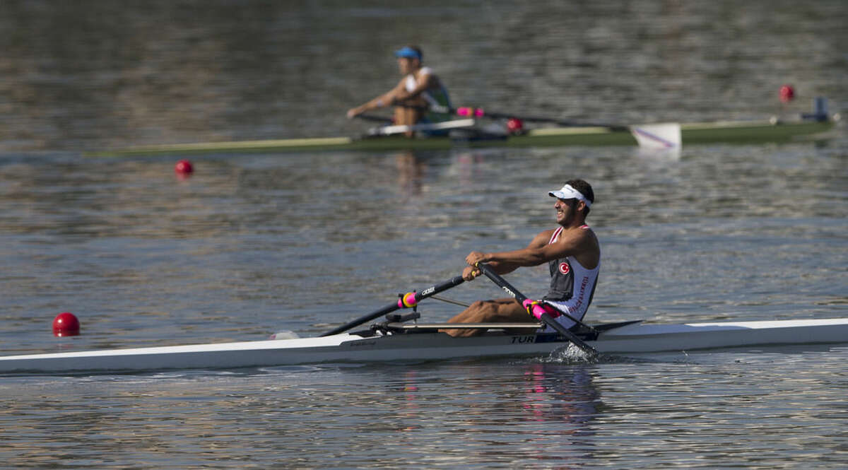 In this Aug. 5, 2015 photo, a rower from Turkey participates in the World Junior Rowing Championships on Rodrigo de Freitas lake in Rio de Janeiro, Brazil. The regatta took place just a week after The Associated Press published an independent five-month analysis of water quality that showed high levels of viruses and in some cases bacteria from human sewage in all of Rio's Olympic and Paralympic water venues, including the Rodrigo de Freitas _ the rowing venue. (AP Photo/Silvia Izquierdo)