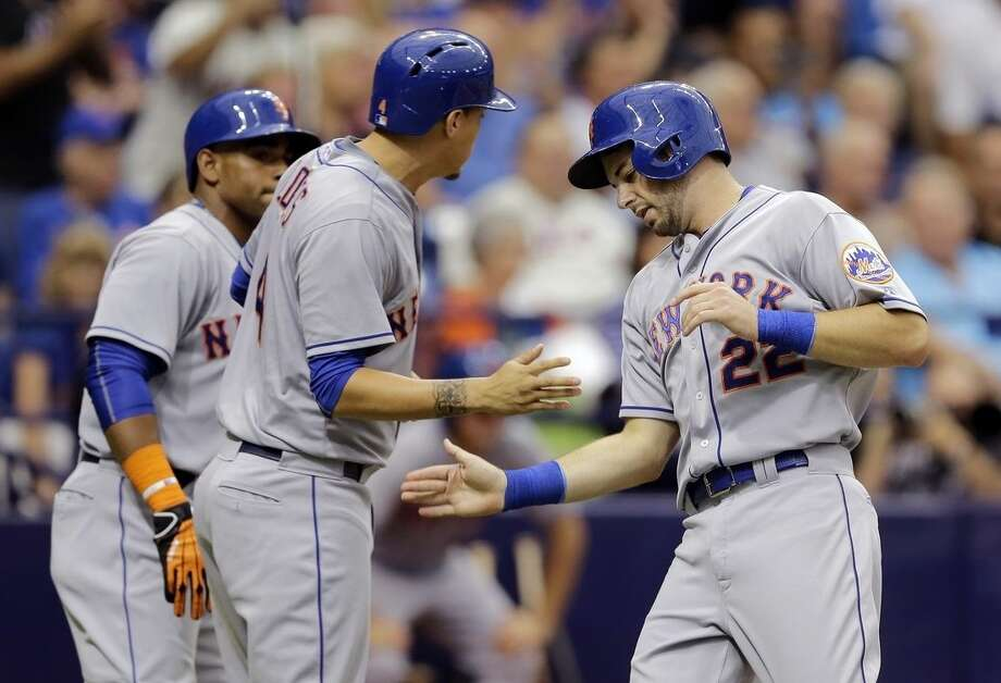 New York Mets' Kevin Plawecki, right, shakes hands with Wilmer Flores, center, after they scored on a two-run single by Daniel Murphy off Tampa Bay Rays starting pitcher Chris Archer during the second inning of an interleague baseball game Sunday, Aug. 9, 2015, in St. Petersburg, Fla. Mets' Yoenis Cespedes, left, looks on. (AP Photo/Chris O'Meara)