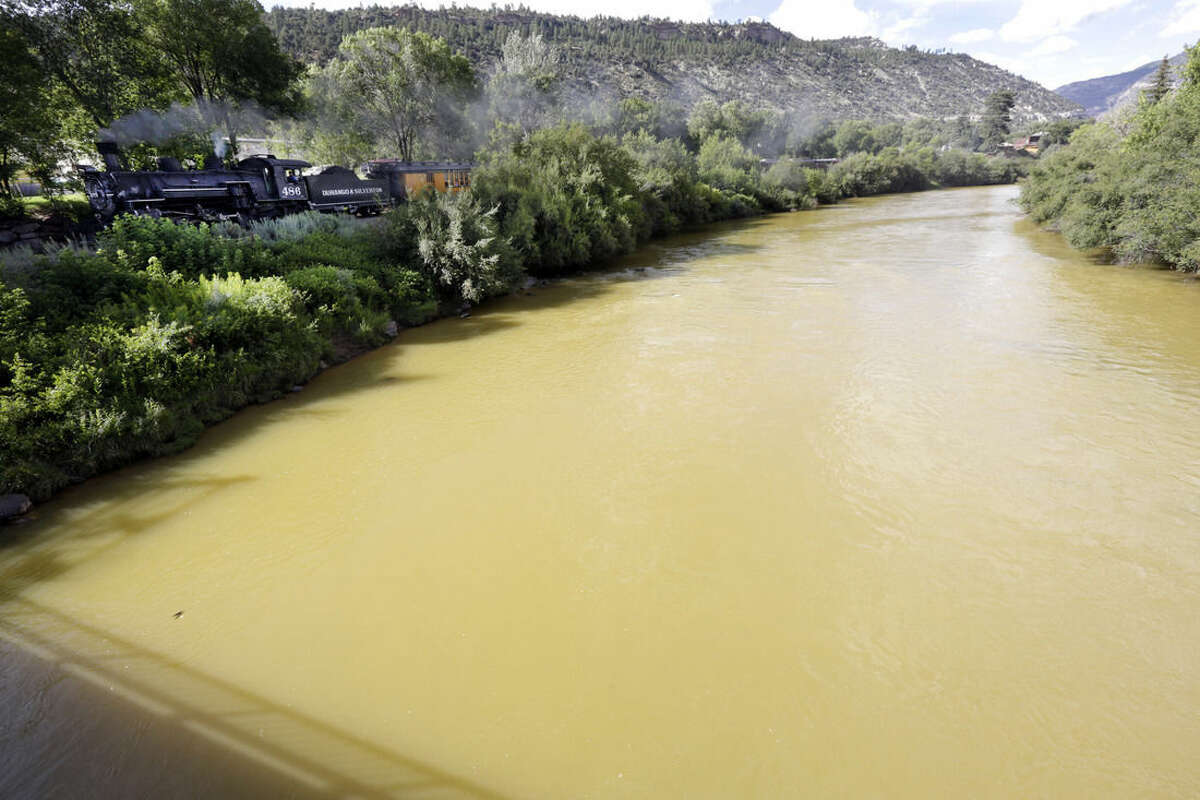 The Animas River is still flowing with toxic waste from the Gold King Mine on Saturday, Aug. 8, 2015, as seen from the 32nd Street Bridge in Durango, Colo., as the Durango & Silverton Narrow Gauge Railroad train goes by. (Jerry McBride/The Durango Herald via AP)