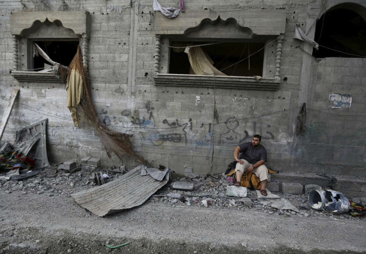 A Palestinian sits in front of the damaged house of Gaza's police chief Taysir al-Batsh after it was hit by an Israeli missile strike in Gaza City, Sunday, July 13, 2014. The strike that hit the home and damaged a nearby mosque as evening prayers ended Saturday, killed at least 18 people, wounded 50 and some people are believed to be trapped under the rubble, said Palestinian Health Ministry official Ashraf al-Kidra. (AP Photo/Hatem Moussa)